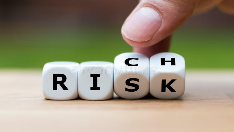 Neem een risico en het krijgen van rijk concept De handdraaien dobbelen en veranderingen het woord 'risico 'voor 'rijken ' stock afbeeldingen