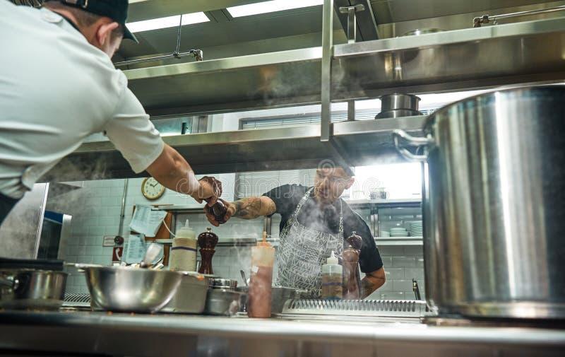 Neem IT Jonge professionele chef-kok in schort die een pepermolen geven aan zijn medewerker terwijl het koken van proces stock foto