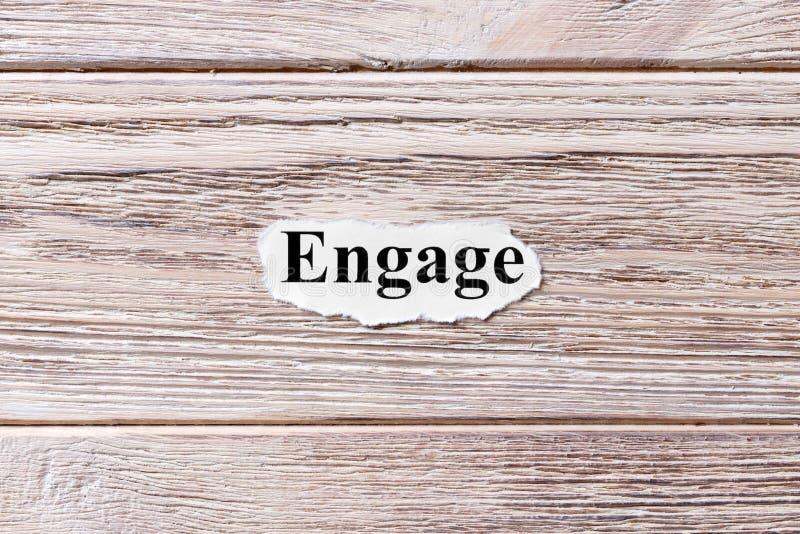 NEEM van het woord op papier in dienst Concept Woorden van ENGAGE op een houten achtergrond stock afbeeldingen