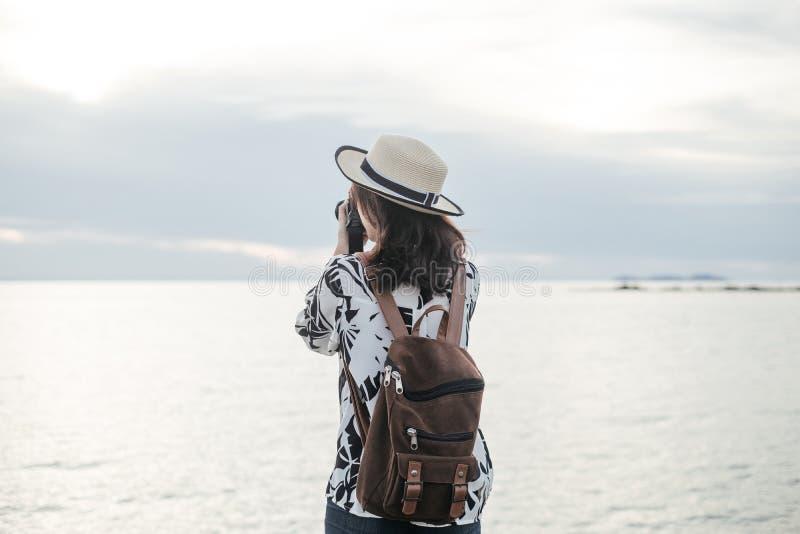 Neemt de reizigers jonge vrouw in de toevallige camera van de kledingsholding en pho royalty-vrije stock afbeeldingen