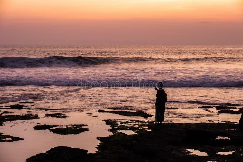 Neemt de silhouet jonge vrouw een foto met mooie overzees op coastl stock fotografie