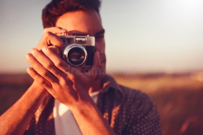 Neemt het close-up mooie portret van de jonge knappe mens met uitstekende camera, een beeld, op gebiedsachtergrond, en op zonsond royalty-vrije stock foto's