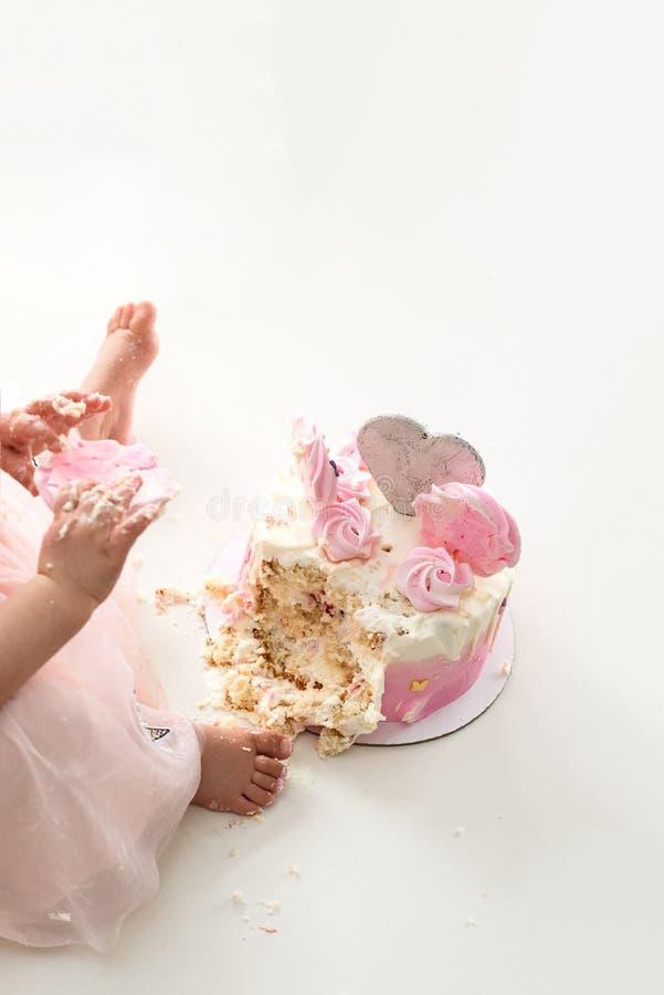 Neerstortings roze cake bij de viering van de eerste verjaardag van het meisje, geruïneerd biscuitgebak, gebroken heemst stock foto's