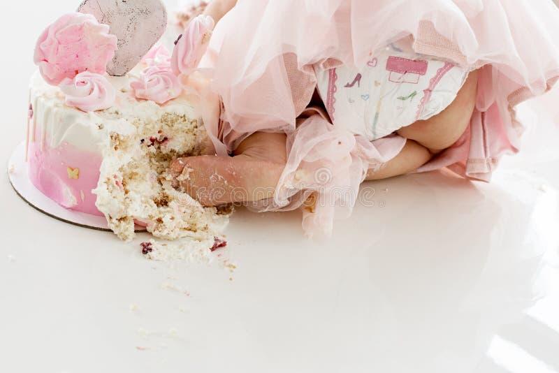 Neerstortings roze cake bij de viering van de eerste verjaardag van het meisje, geruïneerd biscuitgebak, gebroken heemst royalty-vrije stock fotografie