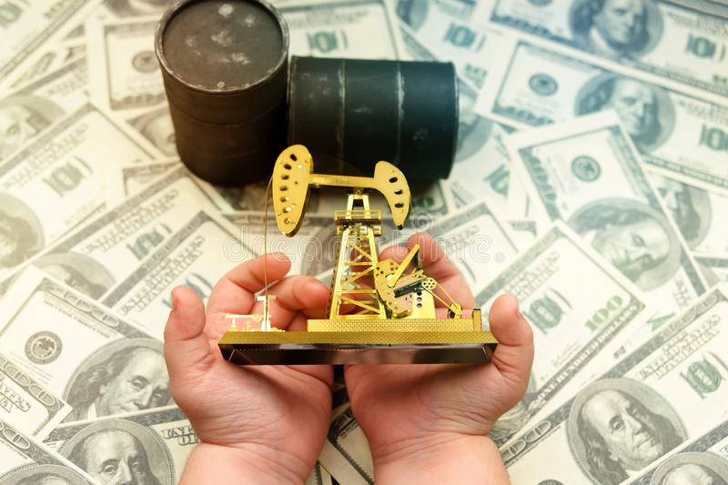 Neftechka in the hands, barrels of oil, bills of American dollars. Business, finance, production, purchase, sale of oil and oil products stock image