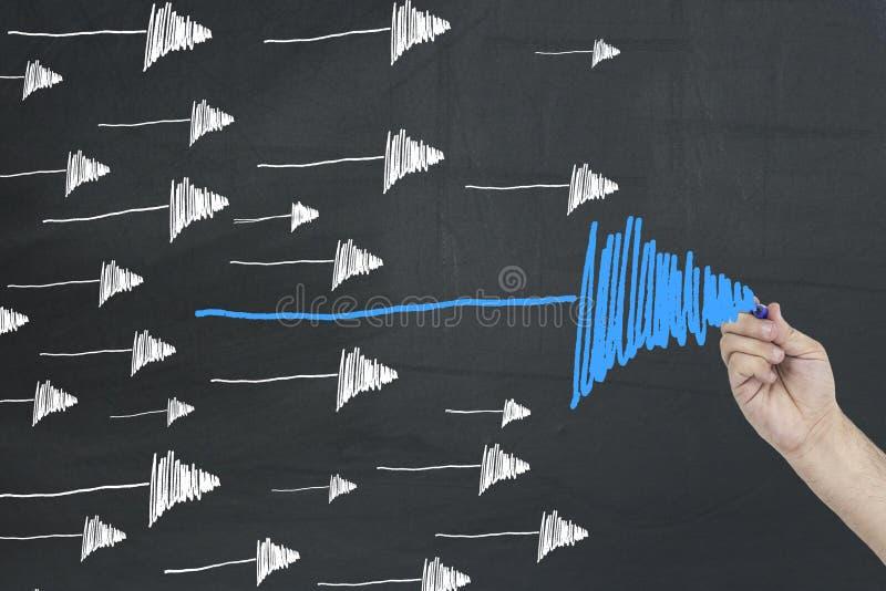 Negócio, conceito da liderança Setas do desenho da mão no quadro preto imagem de stock royalty free