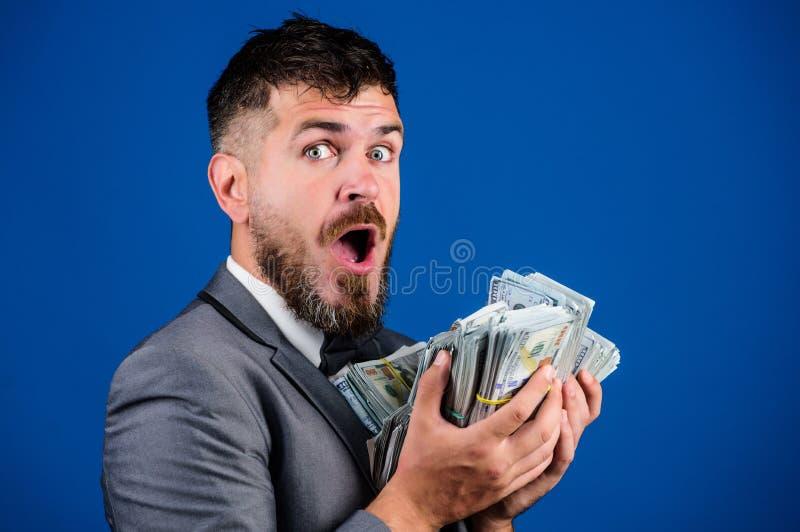 Negócio da transação de dinheiro Pilha rica da posse do vencedor feliz do homem do fundo azul das cédulas do dólar Empréstimos de imagem de stock