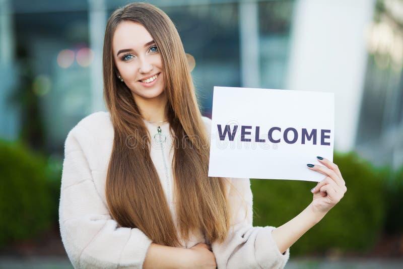 Negócio das mulheres com o cartaz com mensagem bem-vinda foto de stock