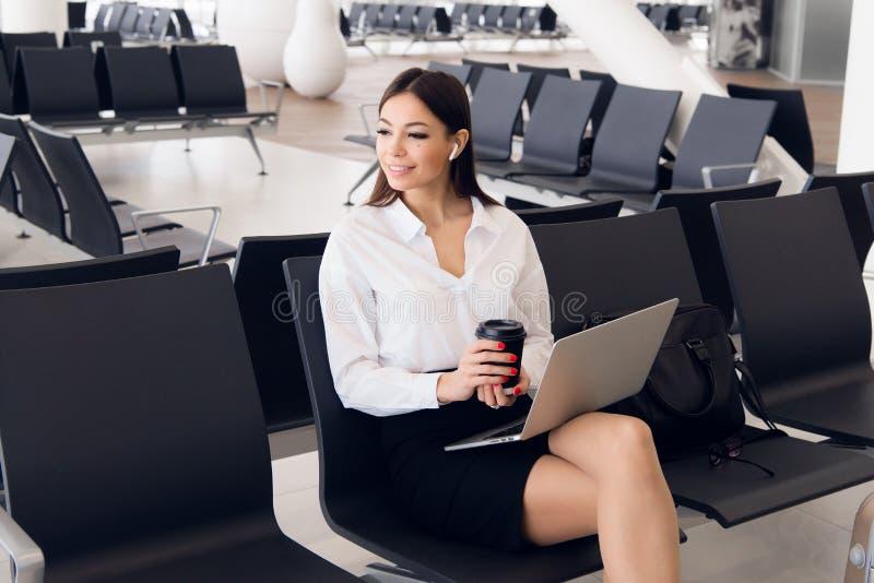 Negócio de Breaktime Mulher de negócio bonita que trabalha no portátil ao esperar seu voo em um aeroporto foto de stock royalty free