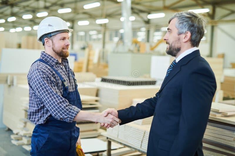 Negócio de conclusão do acionista com a grande fábrica da mobília fotografia de stock royalty free