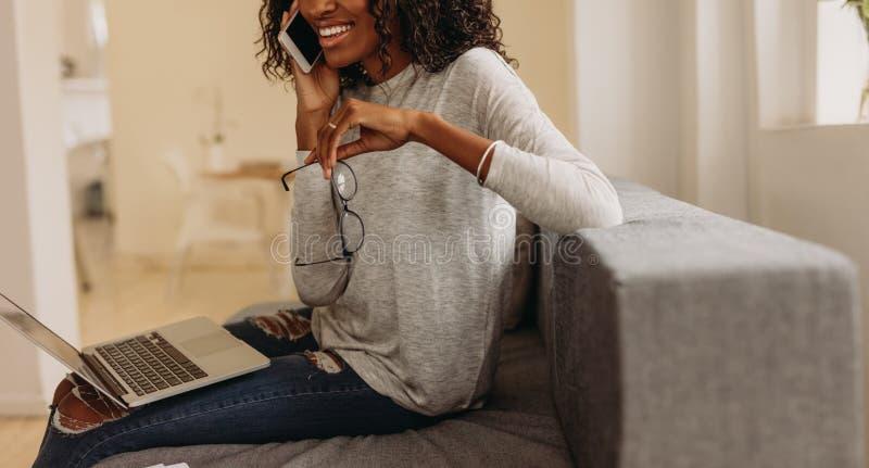 Negócio de controlo da mulher da casa com telefone celular e portátil imagem de stock royalty free