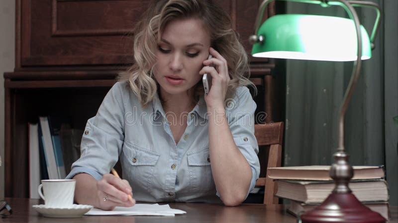 Negócio de fala concentrado da jovem mulher no telefone e nas notas da fatura em sua mesa foto de stock