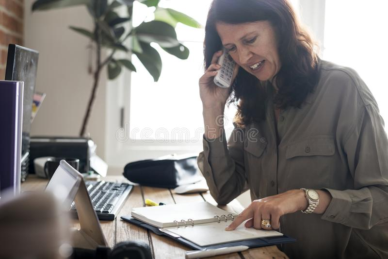 Negócio de fala da mulher caucasiano no telefone imagem de stock