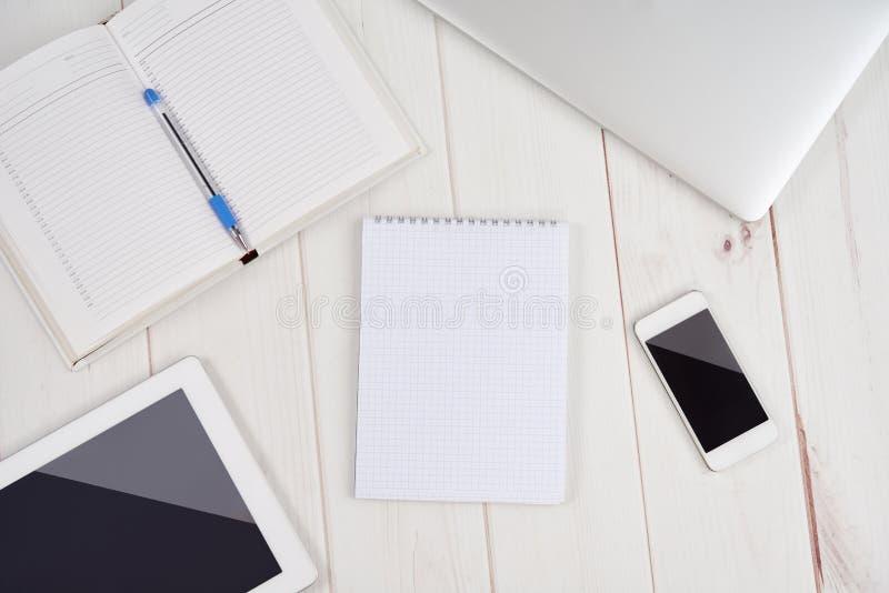 Negócio do local de trabalho caderno vazio vazio, portátil, PC da tabuleta, multidão imagens de stock