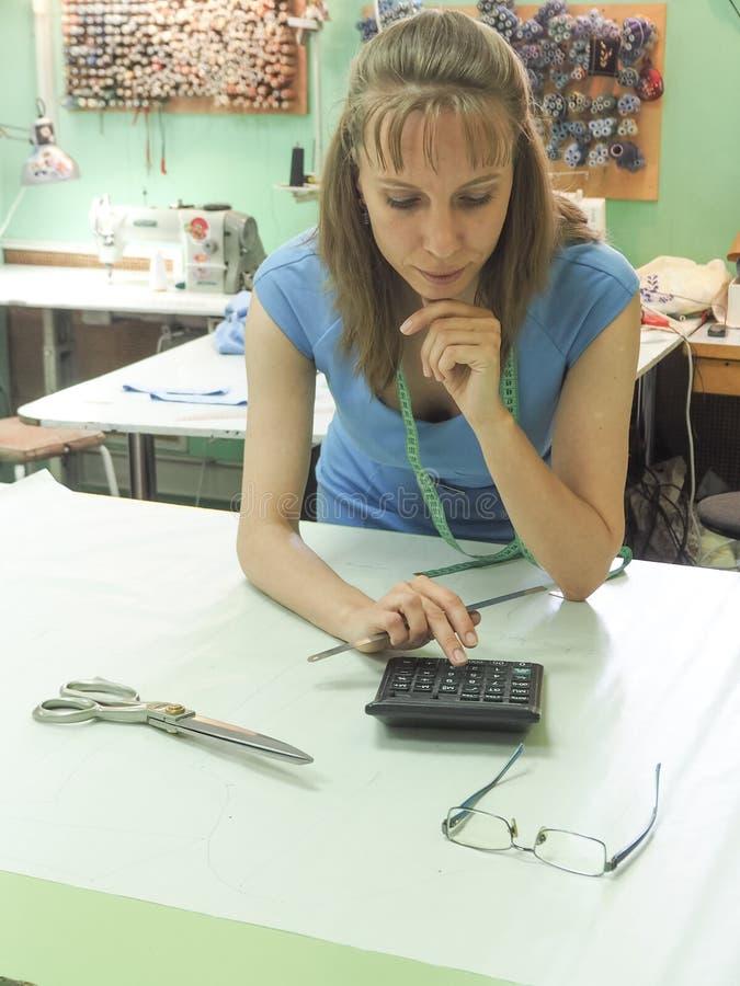 Negócio do ` s do alfaiate Uma mulher que trabalha em testes padrões em um alfaiate pequeno da família fotos de stock royalty free