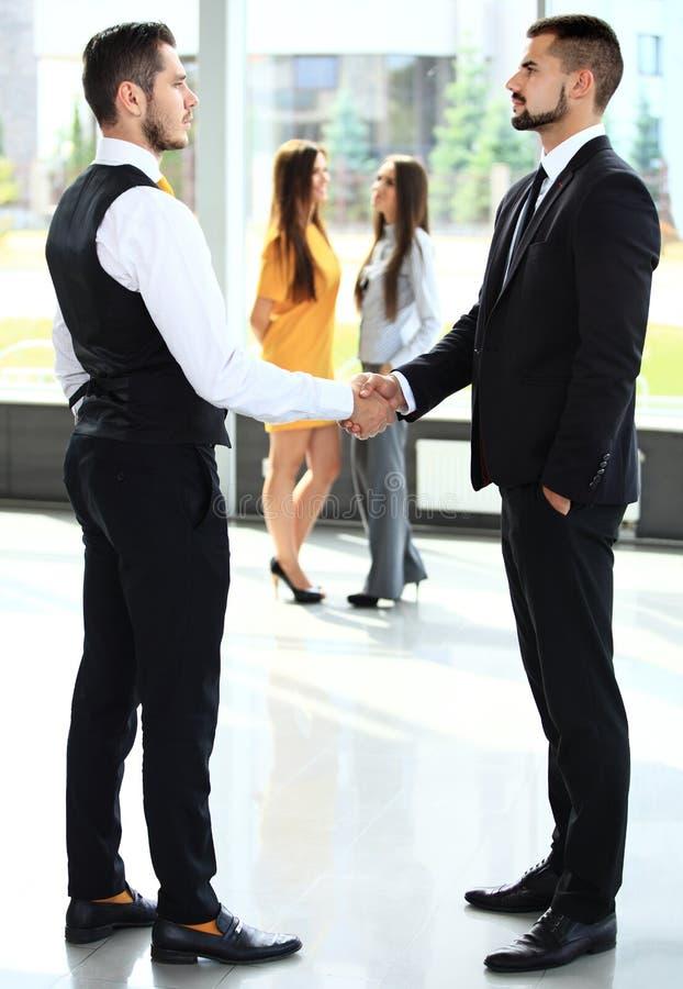 Negócio e conceito do escritório - dois homens de negócios que agitam as mãos imagem de stock royalty free