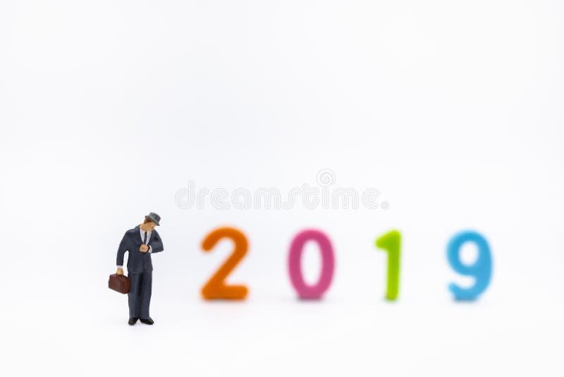 Negócio e 2019 conceitos planejando Feche acima da figura diminuta do homem de negócios com a bolsa que olha ao relógio de pulso  fotos de stock