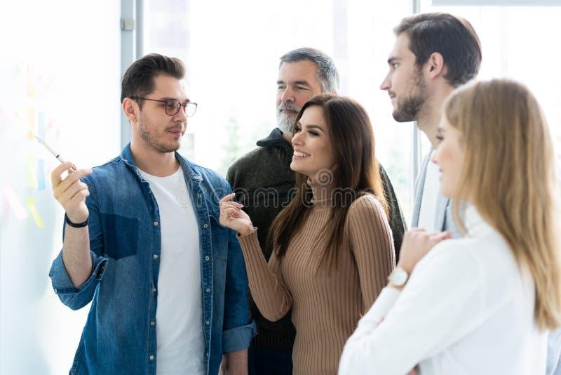 Negócio, educação e conceito do escritório - equipe do negócio com a placa da aleta no escritório que discute algo fotografia de stock royalty free
