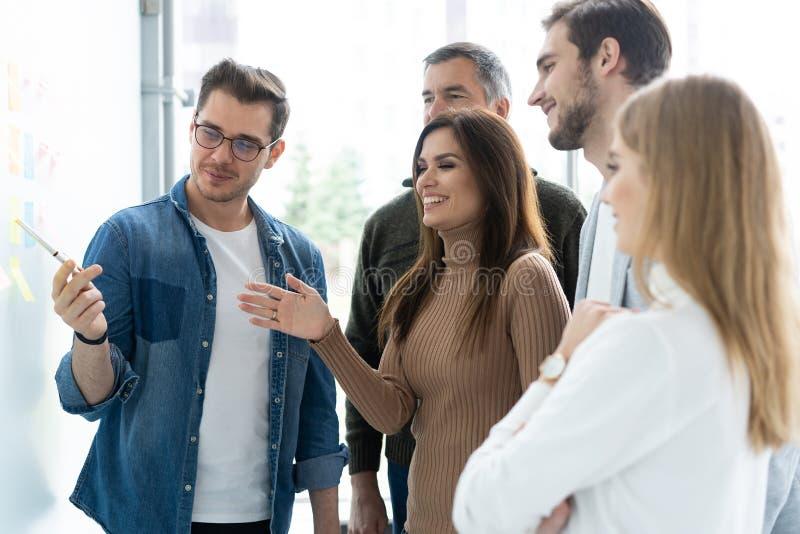 Negócio, educação e conceito do escritório - equipe do negócio com a placa da aleta no escritório que discute algo imagens de stock royalty free