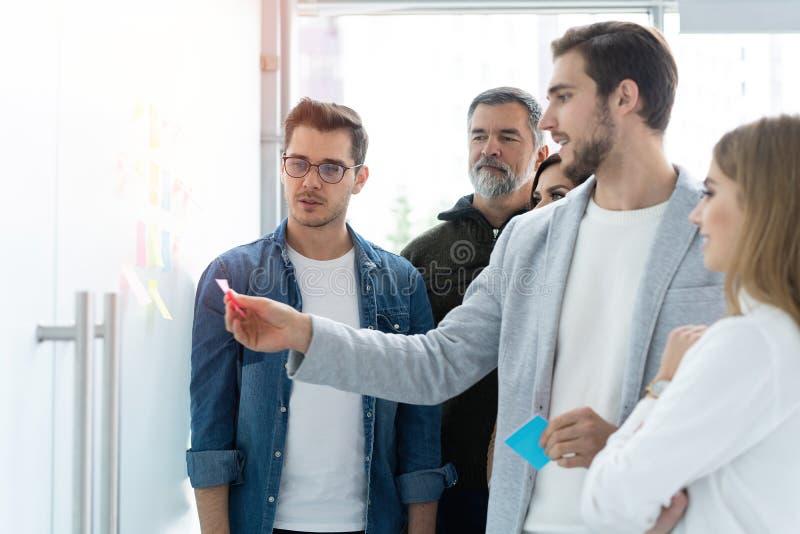 Negócio, educação e conceito do escritório - equipe do negócio com a placa da aleta no escritório que discute algo imagem de stock royalty free