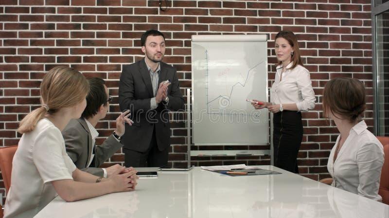 Negócio, educação e conceito do escritório - equipe séria do negócio com a placa da aleta no escritório que discute algo imagem de stock