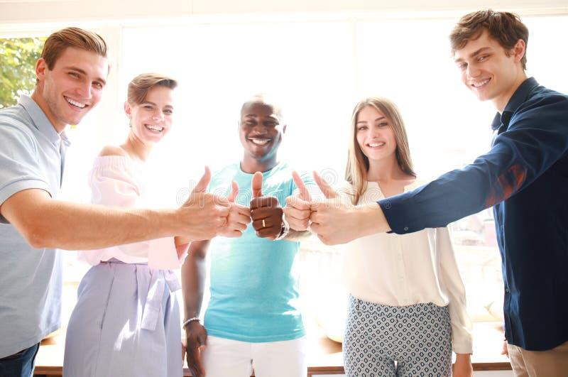 Negócio, partida e conceito do escritório - equipe criativa feliz que mostra os polegares acima no escritório imagens de stock