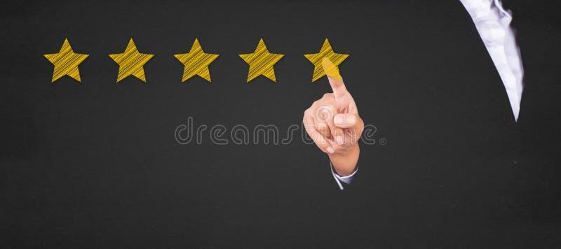 Negócio que aponta a estrela cinco para aumentar a avaliação imagens de stock