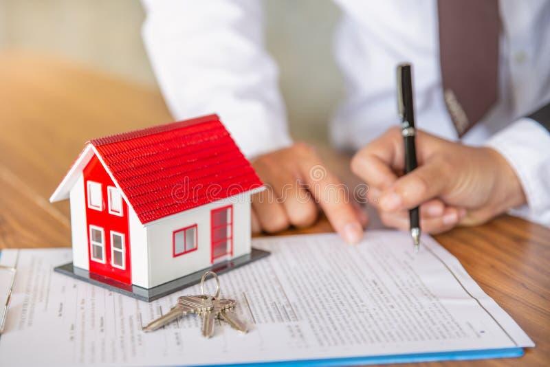 Neg?cio que assina uma casa compra-venda do contrato, casa para o conceito do aluguel, agente do corretor que apresenta e para co fotografia de stock