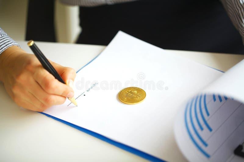 Negócios Mãos do ` s das mulheres com dobrador e pena Bitcoin no Whit fotos de stock royalty free