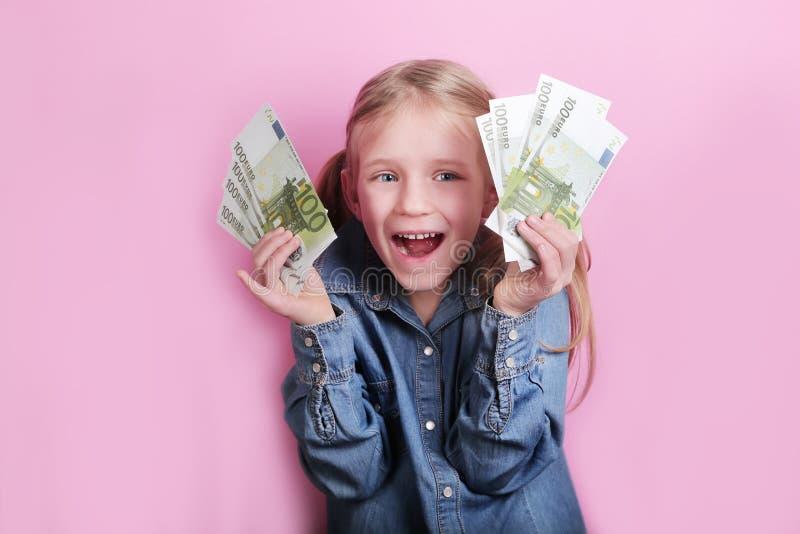 Neg?cio e conceito do dinheiro - menina feliz com euro- dinheiro do dinheiro sobre o fundo cor-de-rosa foto de stock royalty free