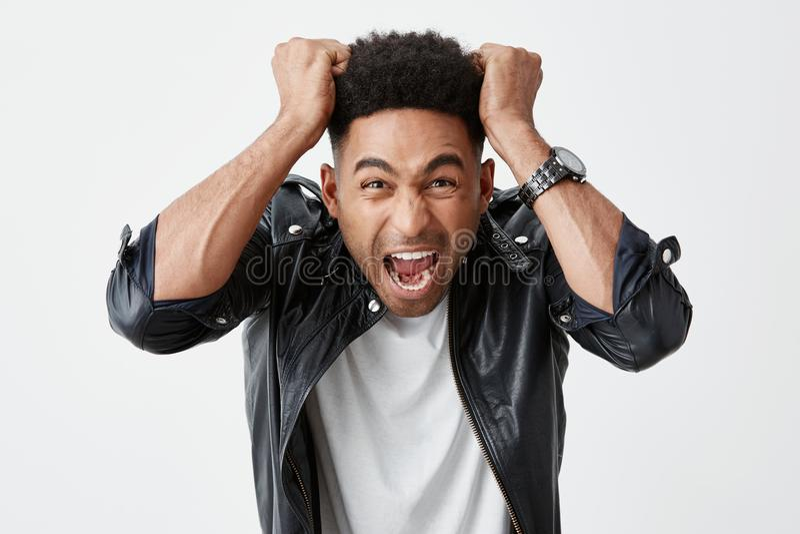 Negatieve emoties Sluit omhoog portret van de jonge mooie zwart-gevilde mens met afrokapsel in witte t-shirt en royalty-vrije stock afbeeldingen