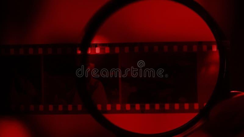 Negativas de la foto debajo de la lupa, buscando para la conexión del crimen, análisis imágenes de archivo libres de regalías