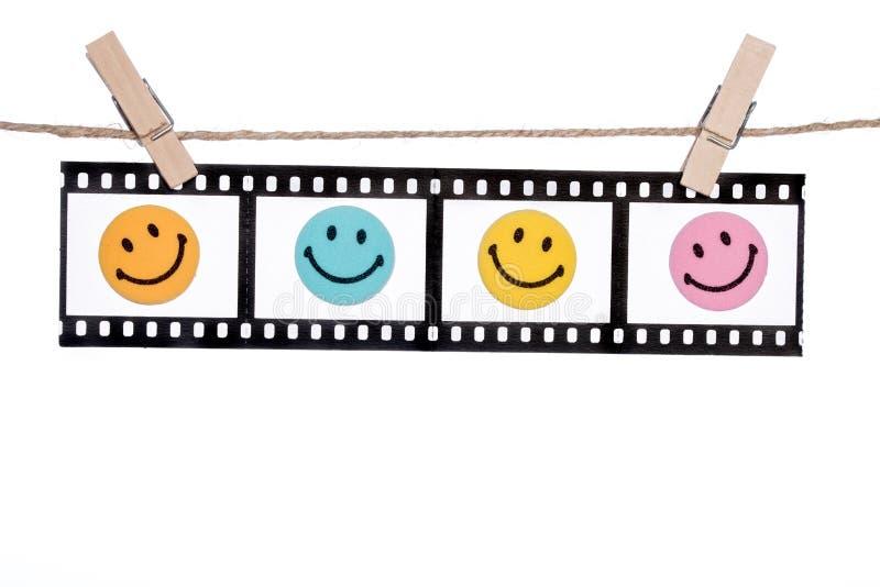 Negativas fotográficas colgantes con la cara sonriente, comedia l feliz foto de archivo