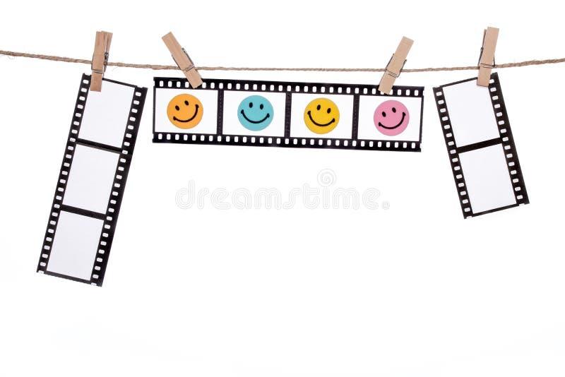 Negativas fotográficas colgantes con la cara sonriente, comedia l feliz fotografía de archivo libre de regalías