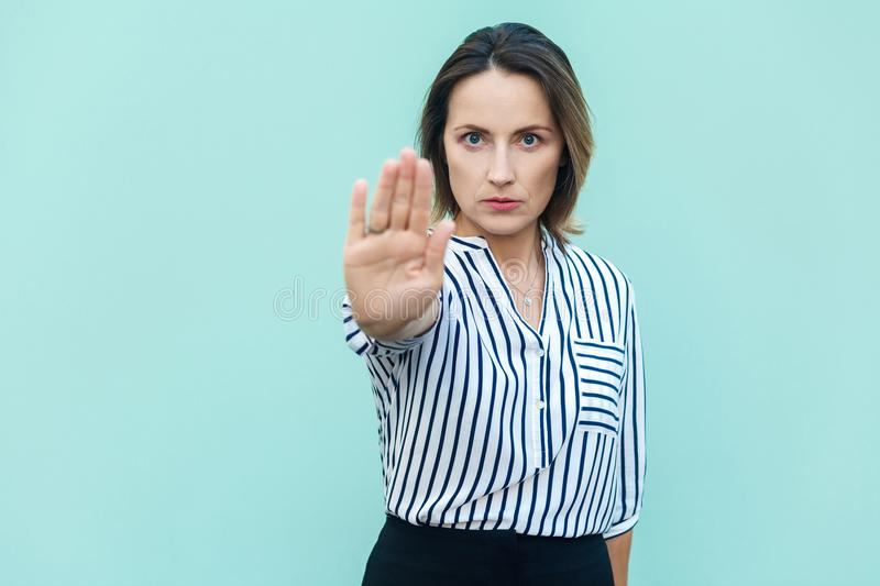 Negative human emotions, feelings, body language. studi. O shot on light blue background. business woman with bad attitude making stop gesture with her palm stock images