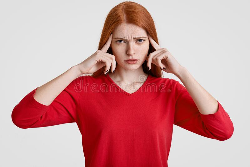 Negative human facial expressions concept. Stressful overworked foxy female has freckled face, keeps both index fingers on temples royalty free stock image