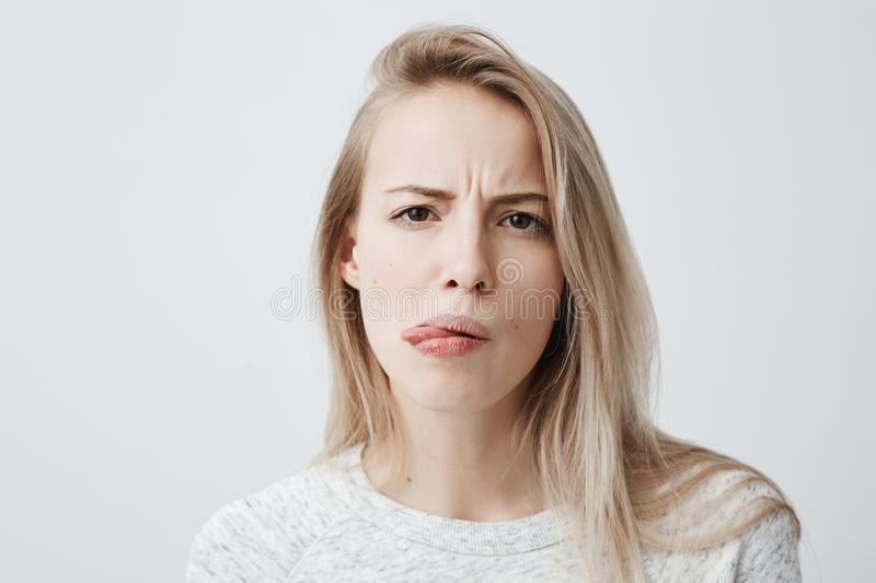 Negative human reaction, feelings and attitude. Close-up portrait of disgusted squeamish blonde woman in casual wear stock photos