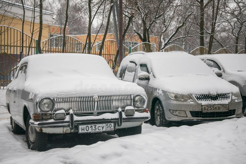The cars, covered with thick layer of snow, in the yard of residential house in provilcial town. Negative impact of heavy snowfall. Yards and surrounding stock image