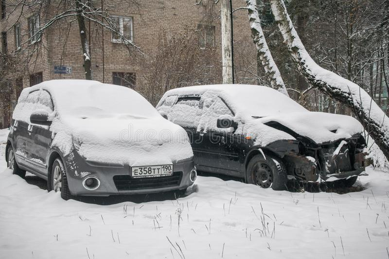 The cars, covered with thick layer of snow, in the yard of residential house in provilcial town. Negative impact of heavy snowfall. Yards and surrounding royalty free stock photo
