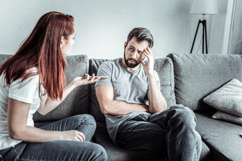 Negativer begeisterter bärtiger Mann, der auf seinen Partner hört stockfotos