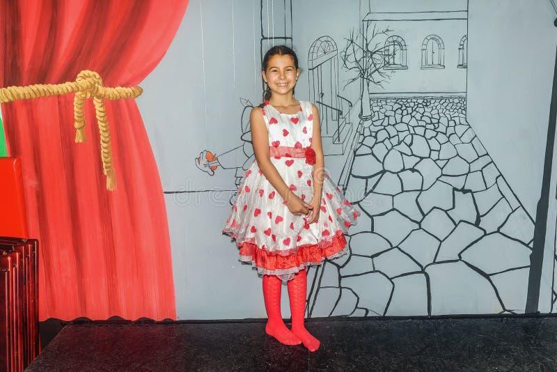 Negen éénjarigen meisje het stellen in een speelkamer in een mooie kleding stock afbeelding