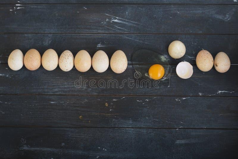 Negen eieren van Turkije en één gebroken ei liggen op een rij op ruwe geverfte houten achtergrond stock foto's