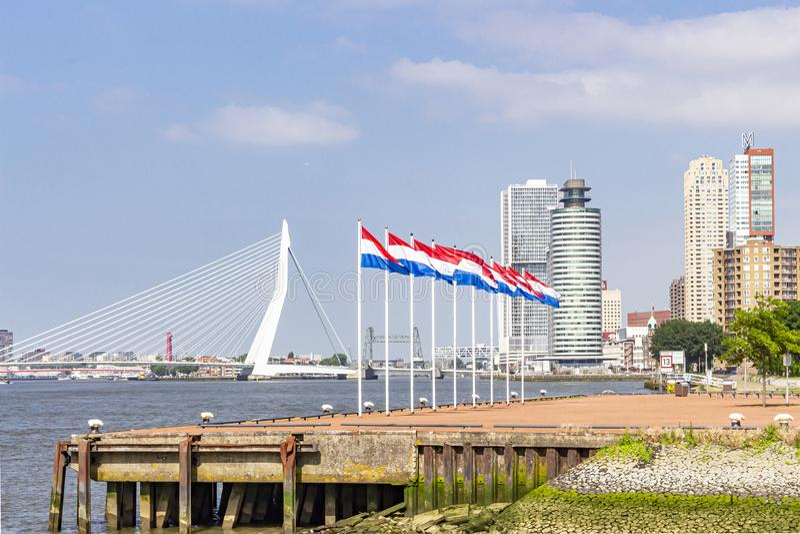 Negen vlaggestokken met de Nederlandse vlag op het hoofd van het schiereiland van Katendrecht met op de achtergrond de Erasmus br stock afbeeldingen
