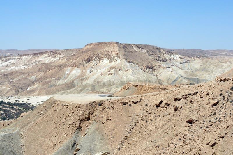 Negevwoestijn van zuidelijk Israël in de zomer Melange van bruine, rotsachtige, stoffige die bergen door wadien worden onderbroke stock fotografie