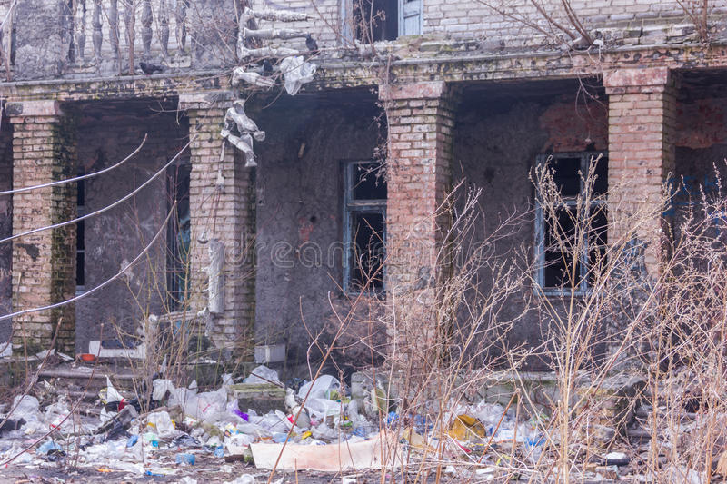 Neglected and abandoned building with garbage around. Disadvantaged areas. Homeless people. stock images