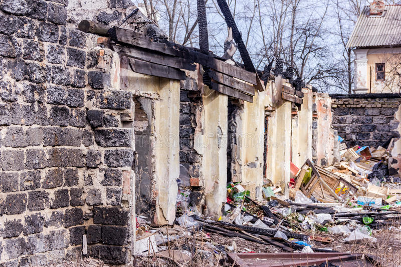 Neglected and abandoned building with garbage around. Disadvantaged areas. Homeless people stock photography