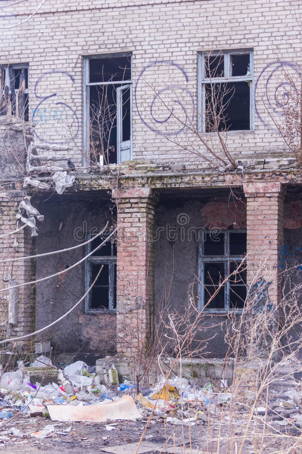Neglected and abandoned building with garbage around. Disadvantaged areas. Homeless people stock images