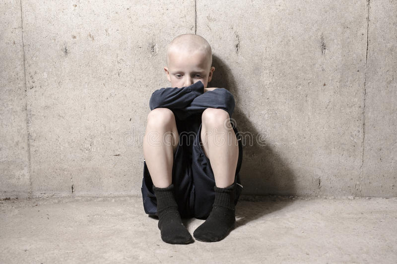 Neglected lonely child leaning at the wall royalty free stock photo