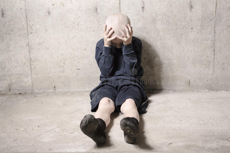 Neglected lonely child leaning at the wall royalty free stock image