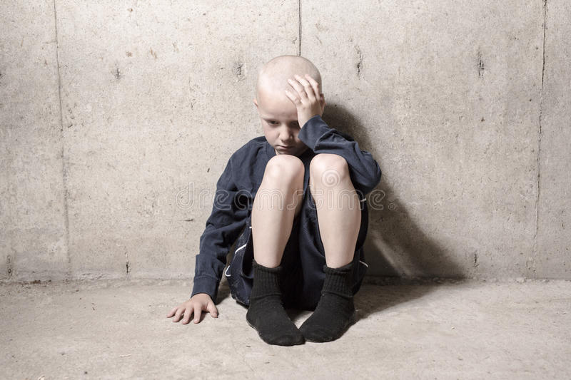 Neglected lonely child leaning at the wall royalty free stock photos